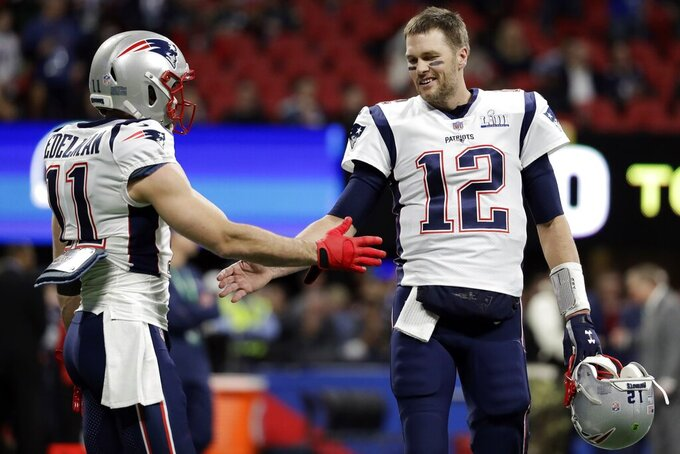 New England Patriots' Julian Edelman (11) greets New England Patriots' Tom Brady (12), before the NFL Super Bowl 53 football game between the Los Angeles Rams and the New England Patriots Sunday, Feb. 3, 2019, in Atlanta. (AP Photo/Jeff Roberson)