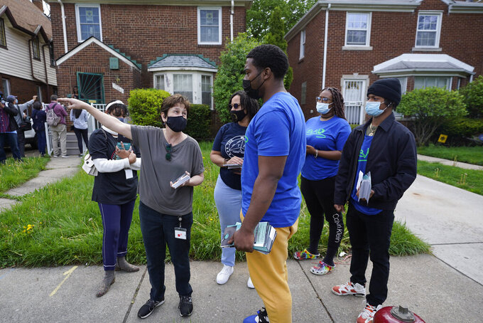Volunteers meet before fanning out to place flyers on homes in Detroit, Tuesday, May 4, 2021. Officials are walking door-to-door to encourage residents of the majority Black city to get vaccinated against COVID-19 as the city's immunization rate lags well behind the rest of Michigan and the United States. (AP Photo/Paul Sancya)