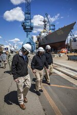 This photo provided by Bath Iron Works shows Chief of Naval Operations Adm. Mike Gilday, center, touring General Dynamics Bath Iron Works in Bath, Maine, on May 10, 2021. He is accompanied by BIW's director of ships completion, Todd Estes, right, and the Navy's Program Executive Officer, Ships, Rear Adm. Tom Anderson. In the background is the future USS Carl M. Levin, DDG 120, which launched later that week. (Jared Morneau/Bath Iron Works via AP)