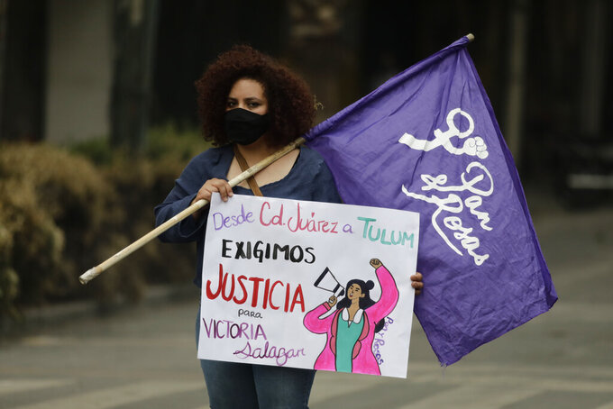 """A woman holds a feminist flag and a sign that reads in Spanish """"From Ciudad Juarez to Tulum we demand justice for Victoria Salazar,"""" during a protest outside of the Quintana Roo state offices in Mexico City, Monday, March. 29, 2021. The demonstrators were protesting the police killing in Tulum, Quintana Roo state, of Salvadoran national Victoria Esperanza Salazar when a female police officer knelt on her back to cuff her. Mexican authorities say an autopsy confirmed that police broke her neck. (AP Photo/Eduardo Verdugo)"""