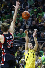FILE - In this Feb. 16, 2020, file photo, Oregon's Payton Pritchard, right, shoots a 3-pointer over Utah's Branden Carlson during the first half of an NCAA college basketball game in Eugene, Ore. Pritchard was selected to the Associated Press All Pac-12 team selected Tuesday, March 10, 2020. Pritchard was also named the AP Pac-12 Player of the Year. (AP Photo/Chris Pietsch, File)