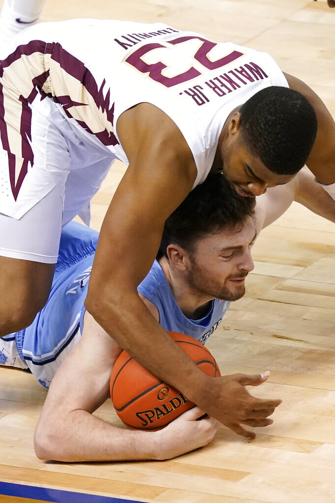 North Carolina guard Andrew Platek, bottom, gathers the ball as Florida State guard M.J. Walker (23) closes in during the first half of an NCAA college basketball game in the semifinal round of the Atlantic Coast Conference tournament in Greensboro, N.C., Friday, March 12, 2021. (AP Photo/Gerry Broome)