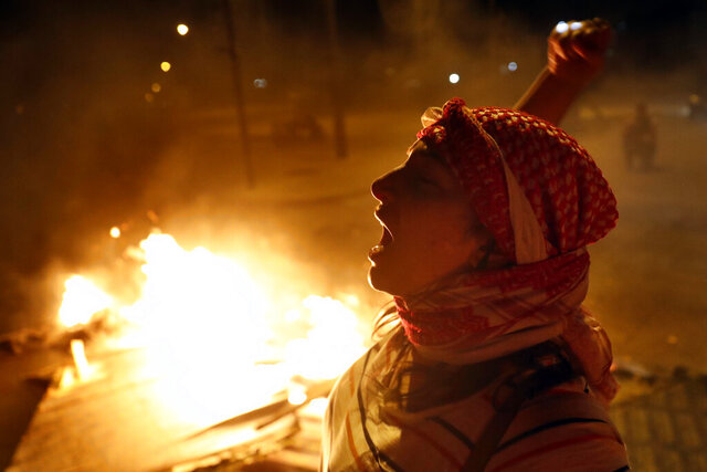 An anti-government protester chants slogans as others burn wood and barriers to block a road during a protest against the political leadership they blame for the economic and financial crisis, in Beirut, Lebanon, Thursday, June 11, 2020. (AP Photo / Hussein Malla)