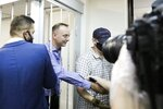 Ivan Safronov, an adviser to the director of Russia's state space corporation, second left, shakes hands with his supporters standing behind bars in a courtroom in Moscow, Russia, Tuesday, July 7, 2020. Safronov, a former journalist who worked as an adviser to the director of the Russian state space corporation, pleaded innocent to the treason charges against him. Ivan Safronov, a former journalist who served as an adviser to Roscosmos head Dmitry Rogozin, was detained in Moscow by agents of the Federal Security Service (FSB), the main KGB successor agency. (Sofia Sandurskaya, Moscow News Agency photo via AP)