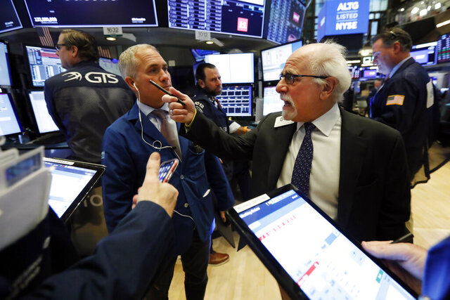 Traders Timothy Nick, left, and Peter Tuchman work on the floor of the New York Stock Exchange, Tuesday, Feb. 18, 2020. Stocks are opening lower on Wall Street after Apple said it would fail to meet its revenue forecast for the current quarter due to the impact of the virus outbreak in China. (AP Photo/Richard Drew)