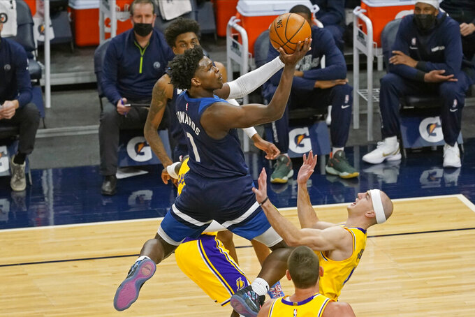 Minnesota Timberwolves' Anthony Edwards, left, lays up knocking over Los Angeles Lakers' Alex Caruso, right, in the first half of an NBA basketball game, Tuesday, Feb. 16, 2021, in Minneapolis. (AP Photo/Jim Mone)