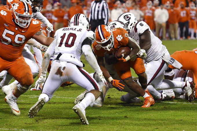 Clemson's Travis Etienne scores a touchdown while defended by South Carolina's R.J. Roderick during the second half of an NCAA college football game Saturday, Nov. 24, 2018, in Clemson, S.C. Clemson won 56-35. (AP Photo/Richard Shiro)
