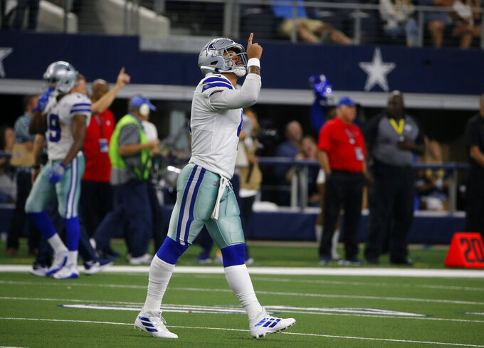 Dallas Cowboys quarterback Dak Prescott (4) celebrates after throwing a touchdown pass to Michael Gallup (13) in the second half of an NFL football game against the Green Bay Packers in Arlington, Texas, Sunday, Oct. 6, 2019. (AP Photo/Michael Ainsworth)