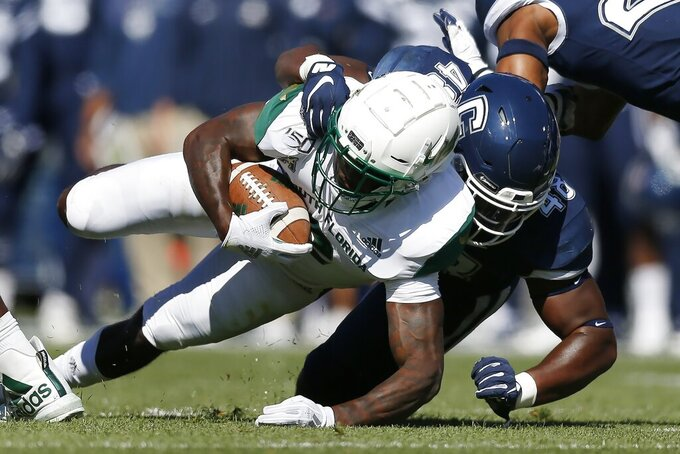 Connecticut defensive lineman Kevon Jones (48) tackles South Florida running back Jordan Cronkrite during the first half of an NCAA college football game in East Hartford, Conn., Saturday, Oct. 5, 2019. (AP Photo/Michael Dwyer)