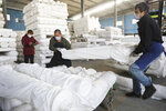 In this photo taken Thursday, Feb. 20, 2020, workers wearing masks move fabric rolls at a textile printing and dyeing plant in Hangzhou in eastern China's Zhejiang province. Factories that make the world's smartphones, toys and other goods are struggling to reopen after a virus outbreak idled China's economy. But even with the ruling Communist Party promising help, companies and economists say it may be months before production is back to normal. (Chinatopix Via AP) CHINA OUT