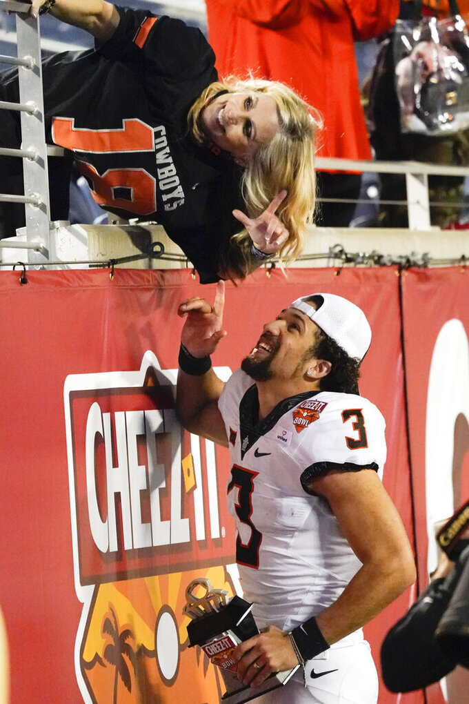 A fan poses for a photo with Cheez-It Bowl MVP Oklahoma State quarterback Spencer Sanders (3) after winning the NCAA college football game against Miami, Tuesday, Dec. 29, 2020, in Orlando, Fla. (AP Photo/John Raoux)