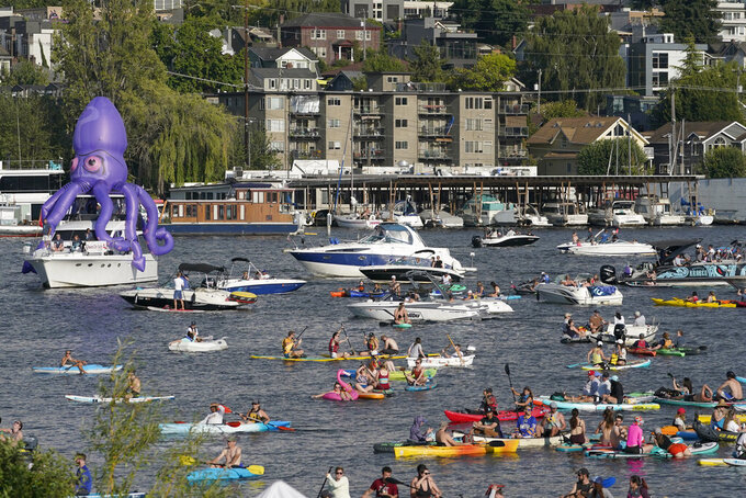 Fans on kayaks and boats, including one sporting a giant inflatable octopus, float on Lake Union, Wednesday, July 21, 2021, during the Seattle Kraken's NHL hockey expansion draft event in Seattle. (AP Photo/Ted S. Warren)