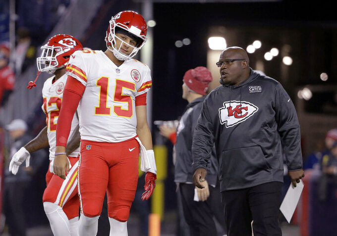 FILE - In this Oct. 14. 2018, file photo, Kansas City Chiefs quarterback Patrick Mahomes listens to offensive coordinator Eric Bieniemy, right, as he warms up for the team's NFL football game against the New England Patriots in Foxborough, Mass. The Miami Dolphins have begun their search for a coach who's ready to lose this year. New England Patriots linebackers coach Brian Flores and Bieniemy, the first candidates to interview for the Dolphins' job, met with them Friday, Jan. 4. Owner Stephen Ross is seeking a replacement for Adam Gase, and wants to rebuild after a 7-9 season. (AP Photo/Steven Senne)