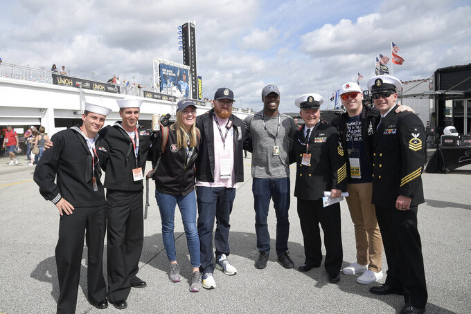 Driver Jesse Iwuji, center right, poses with military personnel and staff from Barstool Sports, including Barstool personality Uncle Chaps, center left, during a practice session for the NASCAR Daytona 500 auto race at Daytona International Speedway Saturday, Feb. 16, 2019, in Daytona Beach, Fla. (AP Photo/Phelan M. Ebenhack)