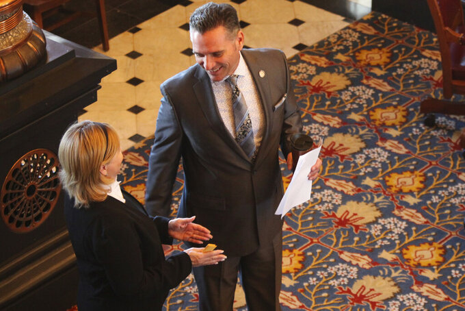 Kansas Senate President Ty Masterson, right, R-Andover, confers with Sen. Caryn Tyson, R-Parker, before the start of the Legislature's last day in session for the year, Wednesday, May 26, 2021, at the Statehouse in Topeka, Kan. Masterson and other Republicans have pushed a resolution through both chambers calling for Democratic Gov. Laura Kelly to end extra unemployment benefits. (AP Photo/John Hanna)