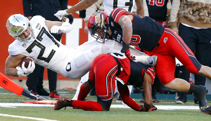 Utah linebacker Cody Barton, upper right, tackles Oregon tight end Jacob Breeland (27) in the first half during an NCAA college football game Saturday Nov. 10, 2018, in Salt Lake City. (AP Photo/Rick Bowmer)