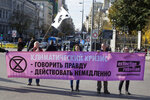 Activists hold a banner written in the Russian language during a protest performance at the Cibeles fountain in central in Madrid, Spain, Tuesday, Dec. 3, 2019. Some 20 activists from the international group called Extinction Rebellion cut off traffic in central Madrid and staged a brief theatrical performance to protest the climate crisis. The activists held up a banner in Russian that read