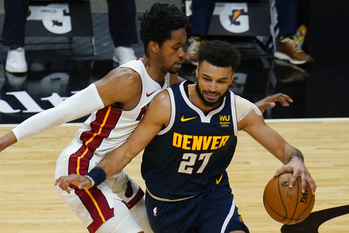 Miami Heat forward KZ Okpala (4) guards Denver Nuggets guard Jamal Murray (27) as he drives to the basket during the first half of an NBA basketball game, Wednesday, Jan. 27, 2021, in Miami. (AP Photo/Marta Lavandier)