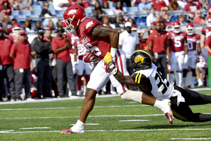 Arkansas receiver Treylon Burks (16) shakes off Pine Bluff defender Paul Reeves (35) as he scores a touchdown in the first half of an NCAA college football game Saturday, Oct. 23, 2021, in Little Rock, Ark. (AP Photo/Michael Woods)