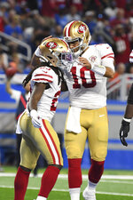 San Francisco 49ers running back JaMycal Hasty (23) celebrates his touchdown run with Jimmy Garoppolo (10) against the Detroit Lions in the first half of an NFL football game in Detroit, Sunday, Sept. 12, 2021. (AP Photo/Lon Horwedel)