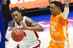 Alabama's John Petty Jr. (23) drives against Tennessee's Keon Johnson (45) in the first half of an NCAA college basketball game in the Southeastern Conference Tournament Saturday, March 13, 2021, in Nashville, Tenn. (AP Photo/Mark Humphrey)