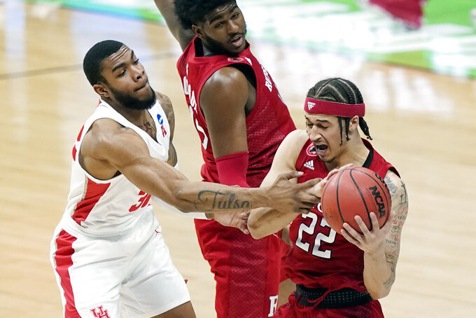 Houston's Reggie Chaney, left, grabs Rutgers' Caleb McConnell (22) during the first half of a college basketball game in the second round of the NCAA tournament at Lucas Oil Stadium in Indianapolis Sunday, March 21, 2021. (AP Photo/Mark Humphrey)