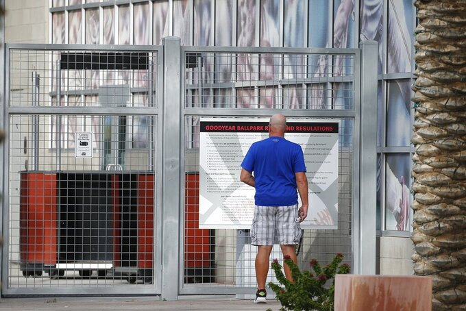 A ticket holder pauses outside a closed Goodyear Ballpark, spring training home of the Cleveland Indians and Cincinnati Reds baseball teams, reading a sign as to where he might get a refund for a canceled game, Thursday, March 12, 2020, in Goodyear, Ariz. Major League Baseball has suspended the rest of its spring training game schedule because if the coronavirus outbreak. MLB is also delaying the start of its regular season by at least two weeks. (AP Photo/Ross D. Franklin)