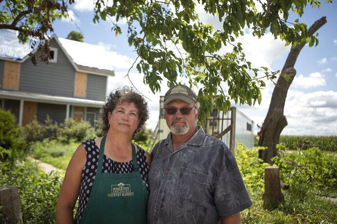 In this Monday, July 15, 2019 photo, John and Karen Pendleton, owners of Pendleton's Country Market, pose in front of their house, east of Lawrence, Kan., which was hit by a tornado in May. The Pendletons are harvesting crops they planted before the storm to sell at the Lawrence Farmers' Market and a nearby nursery. They plan to sell vegetables next year, but have canceled this year's fall pumpkin season, butterfly attraction and Christmastime open house. (James Wooldridge/The Kansas City Star via AP)