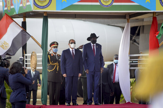 Egypt's President Abdel-Fattah el-Sissi, center-left, and South Sudan's President Salva Kiir, center-right, stand for national anthems after el-Sissi's arrival at the airport in the capital Juba, South Sudan Saturday, Nov. 28, 2020. The Egyptian president is on a one-day visit to discuss bilateral relations. (AP Photo/Maura Ajak)