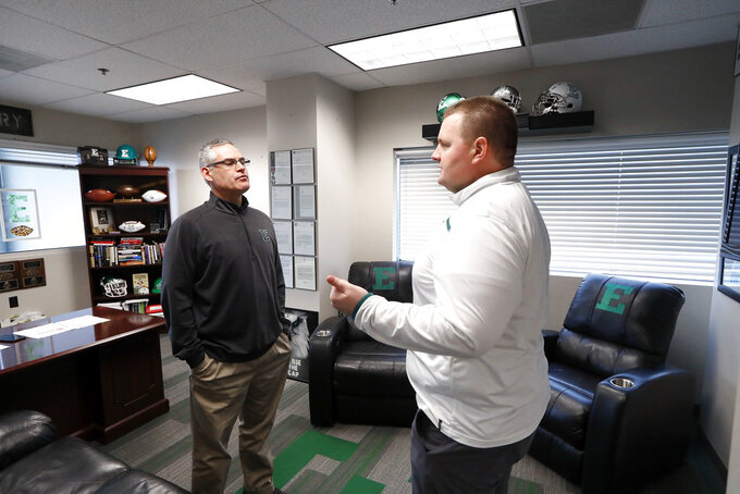 Eastern Michigan football coach Chris Creighton, left, listens to defensive line coach Ben Needham in Ypsilanti, Mich., Monday, Dec. 10, 2018. Eastern Michigan's football team has stepped out of the shadows created by the neighboring University of Michigan and four professional teams just down the road in the Motor City. (AP Photo/Paul Sancya)