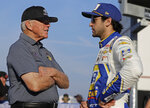 Team owner Joe Gibbs, left, talks with Chase Elliott before qualifications for Sunday's NASCAR Cup Series auto race at Charlotte Motor Speedway in Concord, N.C., Thursday, May 23, 2019. (AP Photo/Chuck Burton)