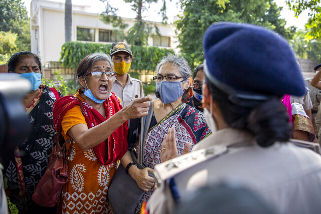 An Indian activist argues with a police officer before being detained by police during a protest in New Delhi, India, Wednesday, Sept. 30, 2020. The gang rape and killing of the woman from the lowest rung of India's caste system has sparked outrage across the country with several politicians and activists demanding justice and protesters rallying on the streets. (AP Photo/Altaf Qadri)