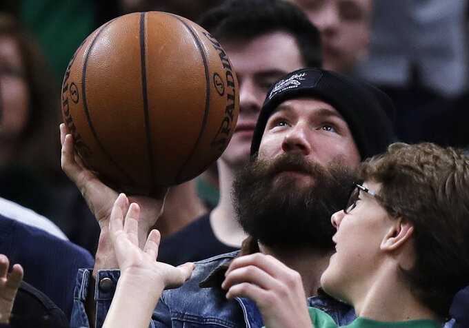 New England Patriots wide receiver Julian Edelman throws back a basketball that he caught courtside during the fourth quarter of an NBA basketball game between the Boston Celtics and Minnesota Timberwolves in Boston, Wednesday, Jan. 2, 2019. The Celtics defeated the Timberwolves 115-102.(AP Photo/Charles Krupa)