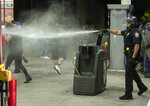 A police officer uses pepper spray to disperse the crowd at an Ez Go gas station after the station was damaged following a protest of the killing of George Floyd, early Saturday, May 30, 2020 in Lincoln, Neb.  Floyd died after being restrained by Minneapolis police officers on Memorial Day.  (Justin Wan/Lincoln Journal Star via AP)
