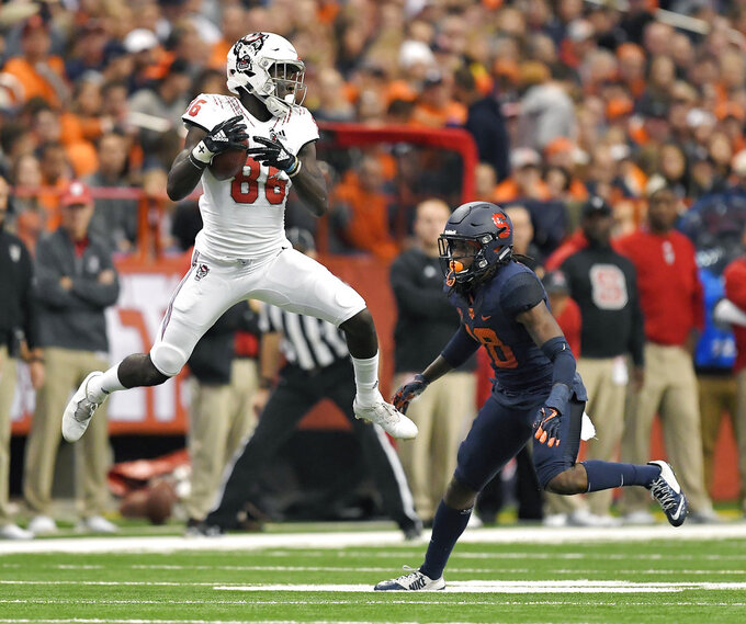 NC State wide receiver Emeka Emezie, left, catches a pass while defended by Syracuse defensive back Scoop Bradshaw during the first half of an NCAA college football game in Syracuse, N.Y., Saturday, Oct. 27, 2018. (AP Photo/Adrian Kraus)
