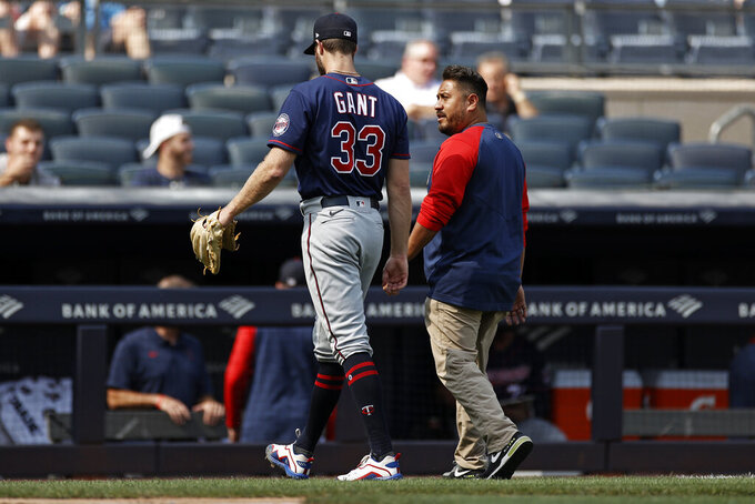 ADDS NAME OF HEAD ATHLETIC TRAINER MICHAEL SALAZAR - Minnesota Twins pitcher John Gant (33) walks off the field with Twins head athletic trainer Michael Salazar after being taken out of a baseball game against the New York Yankees during the first inning Monday, Sept. 13, 2021, in New York. (AP Photo/Adam Hunger)
