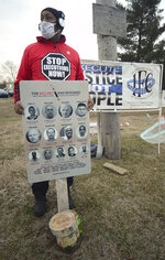 At a protest of the execution of Corey Johnson, Thursday, Jan. 14, 2021, near the Federal Correctional Complex in Terre Haute, Ind., Charles Keith, of Canton, Ohio, holds a sign with all of the mugshots of the 10 men and one woman who have been executed by the federal government since July 14, 2020. (Joseph C. Garza/The Tribune-Star via AP)
