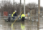 In this Wednesday, March 20, 2019 photo provided by the Missouri State Highway Patrol shows Water Patrol Troopers assisting utility company employees in shutting off natural gas lines in flood waters at Craig, Mo. In northwest Missouri, a levee breached Tuesday, unleashed a torrent that overwhelmed a temporary berm that was built up with excavators and sandbags to protect the small town of Craig, where the 220 residents have been ordered to evacuate.