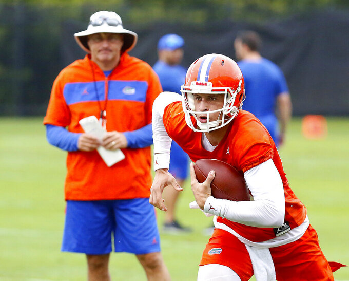 FILE - In this July 26, 2019, file photo, Florida quarterback Feleipe Franks (13) runs with the ball as head coach Dan Mullen watches during an NCAA college football practice in Gainesville, Fla. (Brad McClenny/The Gainesville Sun via AP, File)