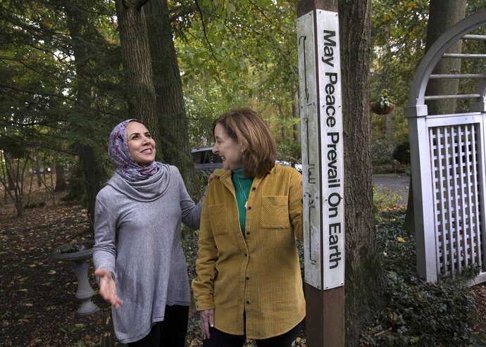 In this Thursday, Oct. 17, 2019, photo, Heba Macksoud, left, of Princeton, N.J., and Sheryl Olitzky, members of the Sisterhood of Salaam Shalom, stand near a Peace Pole written in English and Arabic, as they walk together at Olitzky's home, in North Brunswick, N.J. As the one-year anniversary of Pittsburgh's Tree of Life synagogue attack approaches, and an anti-Semitic shooting in Germany on the holiest day of the Jewish calendar focuses attention anew on the rising tide of global hate crimes against the faith, Jewish and Muslim groups in the U.S. are forging durable alliances in pushing back against crimes targeting their respective communities. (AP Photo/Mel Evans)