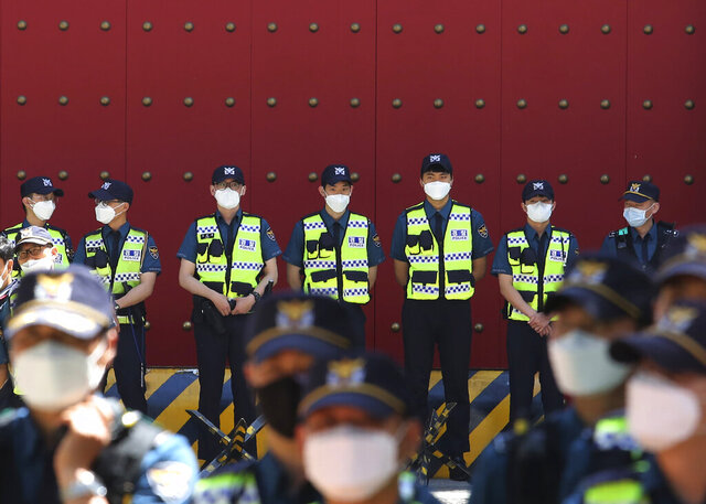 Police officers wearing face masks to help protect against the spread of the new coronavirus stand guard in front of the Chinese embassy in Seoul, South Korea, Monday, June 1, 2020. (AP Photo/Ahn Young-joon)