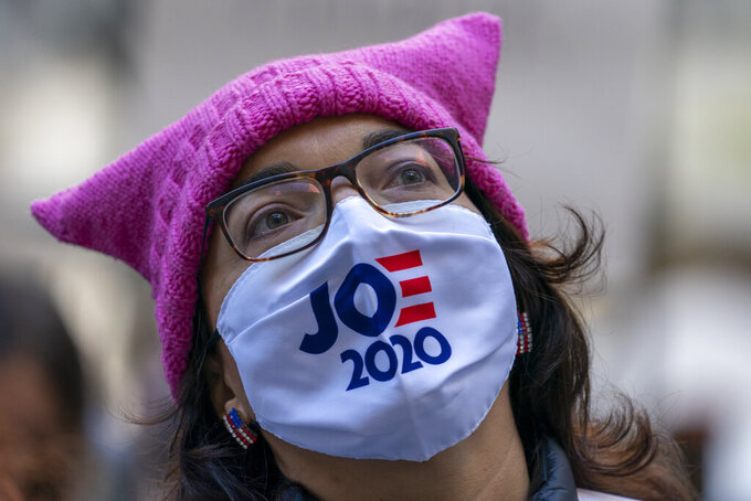 Demonstrators rally during the Women's March outside the New York Stock Exchange, Saturday, Oct. 17, 2020, in New York.  Dozens of Women's March rallies were planned from New York to San Francisco to signal opposition to President Donald Trump and his policies, including the push to fill the seat of late Supreme Court Justice Ruth Bader Ginsburg before Election Day. (AP Photo/Mary Altaffer)