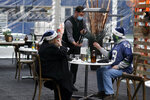 "Tom Gallagher, right, wears a Seattle Seahawks Julian Peterson jersey and holiday hat as he is offered a bottle of wine by a server while dining with his wife Debbie in an outdoor dining tent set up on the turf at Lumen Field, Thursday, Feb. 18, 2021, in Seattle. The couple, who are Seattle Seahawks season ticket holders, were celebrating their 45th anniversary by taking part in the ""Field To Table"" event at the Seahawks' home stadium on the first night of several weeks of dates that offer four-course meals cooked by local chefs and served at tables socially distanced as a precaution against the COVID-19 pandemic. (AP Photo/Ted S. Warren)"