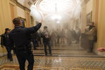 FILE - In this Wednesday, Jan. 6, 2021 file photo smoke fills the walkway outside the Senate Chamber as supporters of President Donald Trump are confronted by U.S. Capitol Police officers inside the Capitol in Washington. Right-wing extremism has previously mostly played out in isolated pockets of America or in smaller cities. In contrast, the deadly attack by rioters on the U.S. Capitol targeted the very heart of government. It brought together members of disparate groups, creating the opportunity for extremists to establish links with each other.  (AP Photo/Manuel Balce Ceneta, File)
