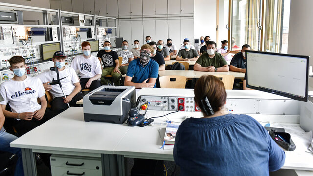 FILE - In this Thursday, Aug. 13, 2020 file photo, students of the Robert-Koch vocational college sit with face masks in the classroom during computer science lessons in Dortmund, Germany. Despite a spike in coronavirus infections, authorities in Europe are determined to send children back to school. At least 41 of Berlin's 825 schools reported virus cases as classes resumed this month, and thousands of students have been quarantined around the country. But Germany is determined not to close schools anew, so they're sending individual students or classes into quarantine instead. (AP Photo/Martin Meissner, File)