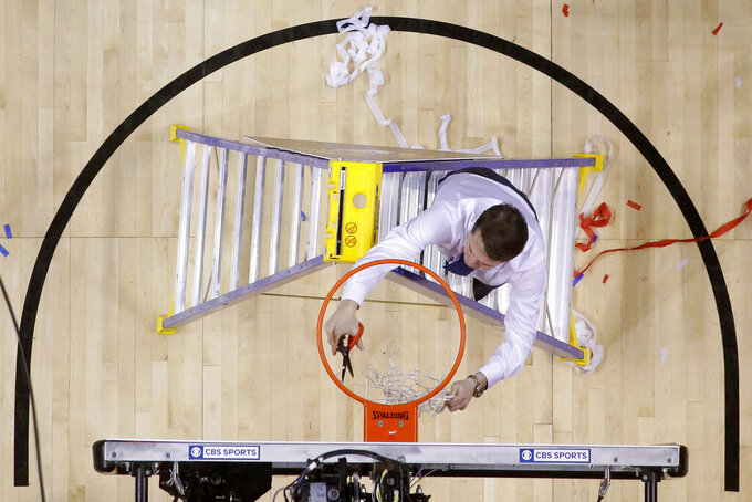 Saint Louis coach Travis Ford cuts the net after the team defeated St. Bonaventure during an NCAA college basketball game in the Atlantic 10 men's tournament final, Sunday, March 17, 2019, in New York. Saint Louis won 55-53. (AP Photo/Julio Cortez)
