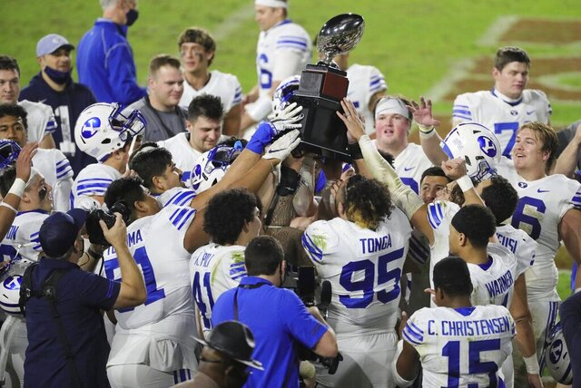 BYU players hold the championship trophy after defeating UCF in the Boca Raton Bowl NCAA college football game at FAU Stadium in Boca Raton, Fla. Tuesday, Dec. 22, 2020.(Al Diaz/Miami Herald via AP)