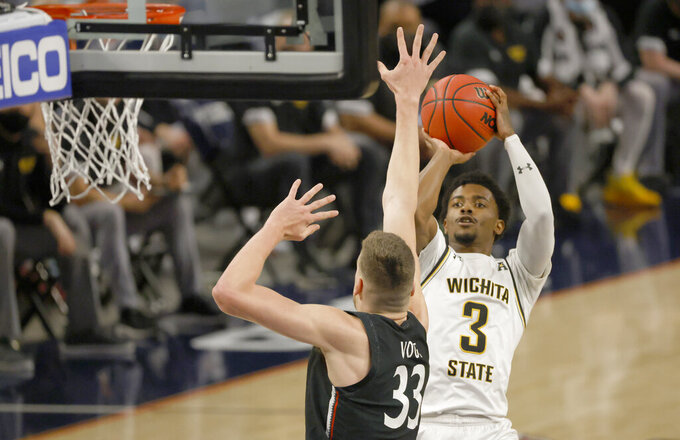 Wichita State guard Alterique Gilbert (3) shoots over Cincinnati center Chris Vogt (33) during the first half of an NCAA college basketball game in the semifinal round of the American Athletic Conference men's tournament Saturday, March 13, 2021, in Fort Worth, Texas. (AP Photo/Ron Jenkins)