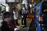 People wearing mask as a precaution against coronavirus outbreak, wait for public transport in Jakarta, Indonesia, Thursday, Dec. 3, 2020. (AP Photo/Dita Alangkara)
