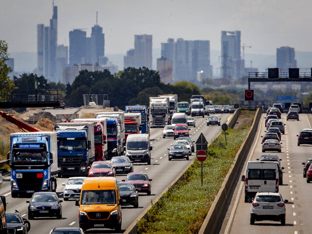 Cars and trucks drive on the main highway around Frankfurt, Germany, Tuesday, Aug. 4, 2020. In background the buildings of the banking district. (AP Photo/Michael Probst)